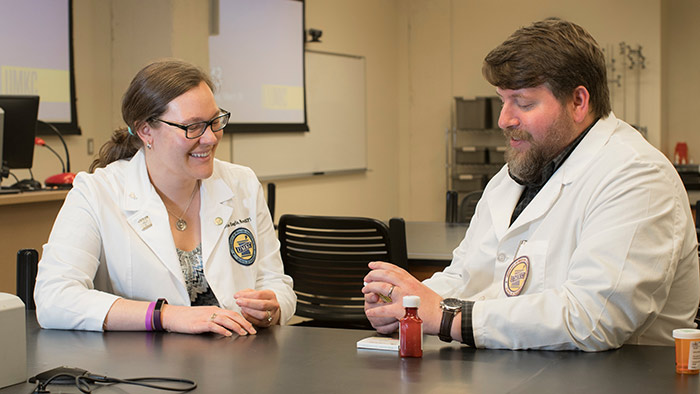 Mica Henry speaking with pharmacy professor inside lab.