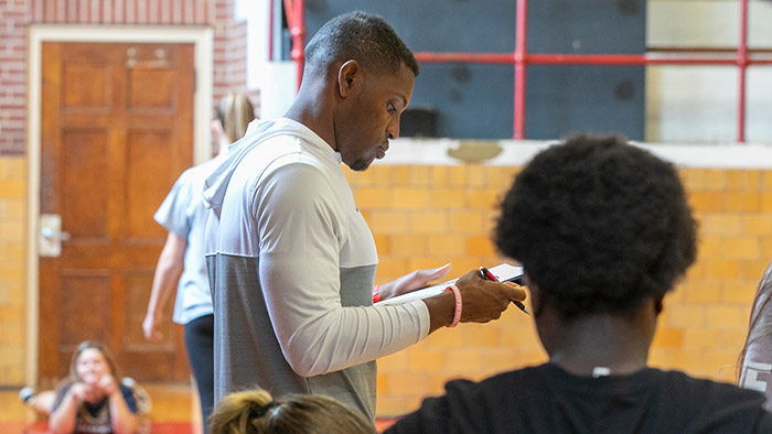 Sean Nevills writing on clipboard during physical education class.