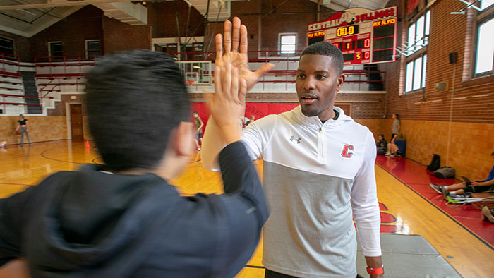 Sean Nevills congratulating PE student.